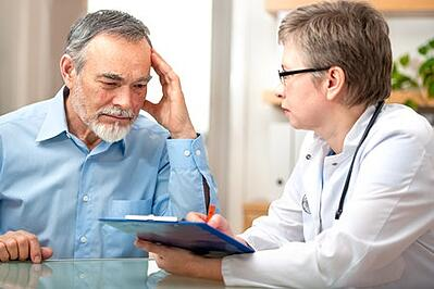Man Speaking With Doctor About Cancers Associated With Military Radiation Exposure